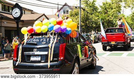Babylon, New York, Usa - 28 June 2020: Decorated In Rainbow Colors Cars Driving Up Deer Park Ave In