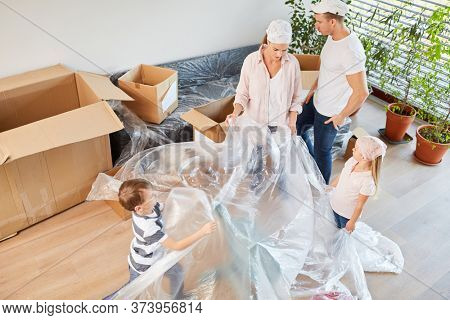 Parents and children as home improvement with protective film renovate house together