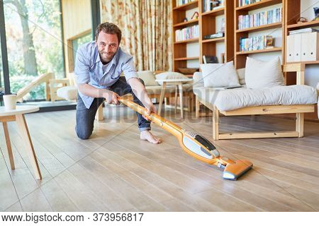 Houseman with vacuum cleaner vacuuming in the living room during spring cleaning