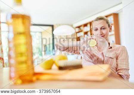 Housewife uses lemons as a home remedy for cleaning a glass bowl