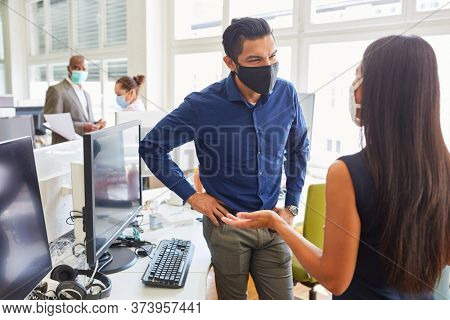 Two business people with face mask because of Covid-19 in a start-up office during a meeting