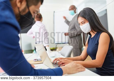 Businessmen wearing a Covid-19 mask and corona virus work together in the open-plan office