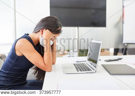 Business woman wearing face mask because of Covid-19 sits with burnout due to overload on computer