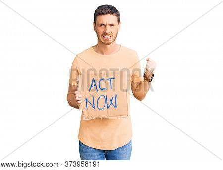 Handsome young man with bear holding act now banner annoyed and frustrated shouting with anger, yelling crazy with anger and hand raised