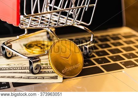 Shopping Cart With Golden Ether Coins Or Ethereum Network Exchange And 100 Dollars On Keyboard Of La