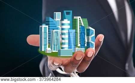 Unrecognizable Businessman Holding Futuristic City Model With Highrise Buildings Over Blue Backgroun