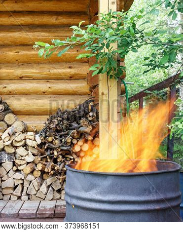 Garbage Incineration In Rusty Metal Barrel. High Flame. Harm To Environment And Human Health