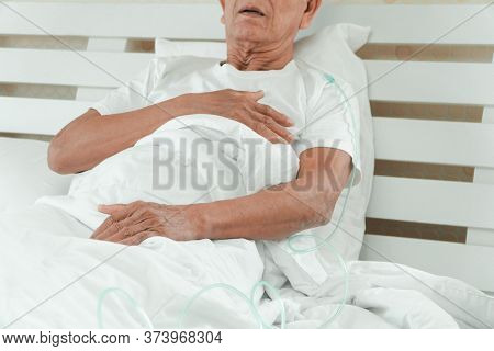 Sad Senior Man Lying On The Hospital Bed And With A Nasal Breathing Tube For Treatment Respiratory.
