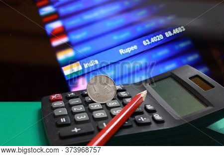 One Rupee Coin Of India And Pencil On The Calculator With Digital Board Of Currency Exchange Money B