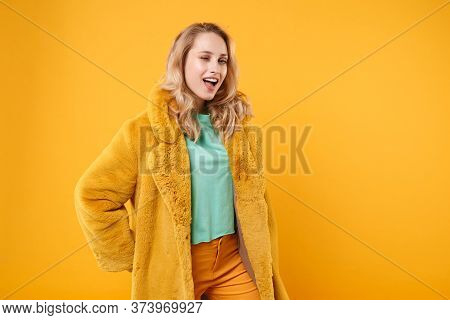 Funny Stunning Young Blonde Woman Girl In Yellow Fur Coat Posing Isolated On Orange Background Studi