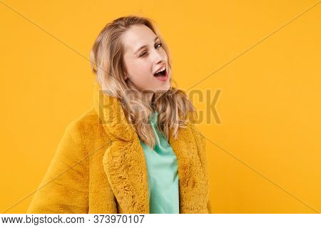 Funny Cheerful Young Blonde Woman Girl In Yellow Fur Coat Posing Isolated On Orange Background Studi