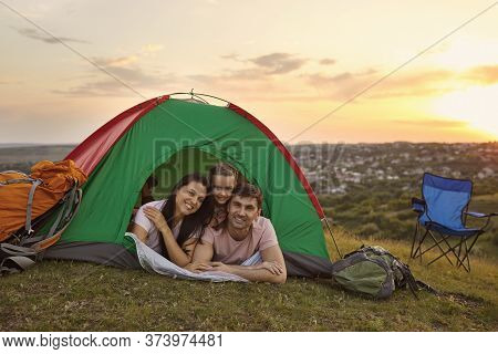 Happy Family With Child On Camping Trip Relaxing Inside Tent. Caring Parents And Their Daughter Rela