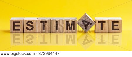 Word Estimate Is Made Of Wooden Building Blocks Lying On The Table And On A Light Yellow Background.