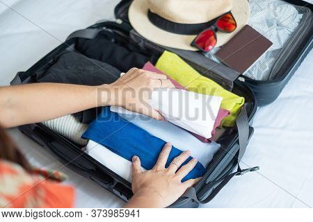 Young Adult Female Packing Luggage For Summer Vacation. Woman Tourist Checking List Travel Accessori