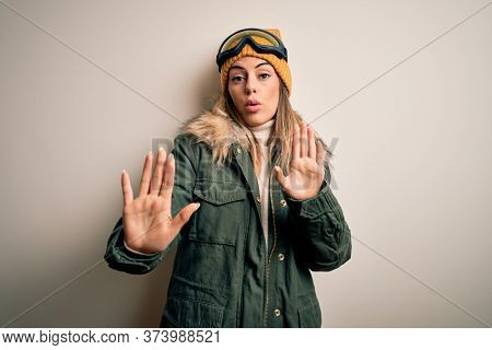 Young brunette skier woman wearing snow clothes and ski goggles over white background Moving away hands palms showing refusal and denial with afraid and disgusting expression. Stop and forbidden.