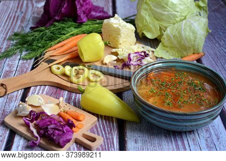 Cooking Soup And Slicing Fresh Vegetables On A Rustic Kitchen Worktop, Healthy Eating Concept. Close