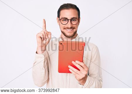 Young handsome man using touchpad device surprised with an idea or question pointing finger with happy face, number one