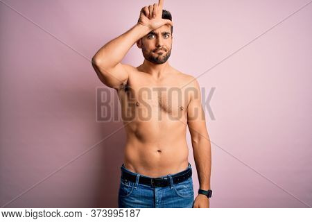Young handsome strong man with beard shirtless standing over isolated pink background making fun of people with fingers on forehead doing loser gesture mocking and insulting.