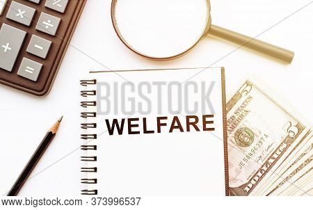 The Word Welfare Written On Notebook On Table With Calculatir, Magnifier, Pencil And Dollars