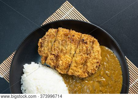 Tonkatsu Curry Rice (japanese Deep-fried Pork Cutlet With Curry Rice). Top View On Black Background.