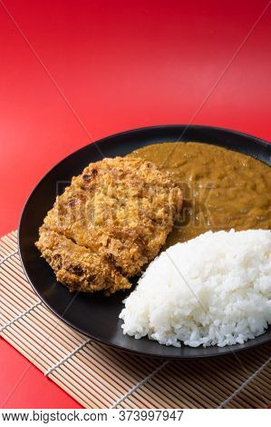 Tonkatsu Curry Rice (japanese Deep-fried Pork Cutlet With Curry Rice). On Red Background.
