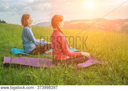 Yoga in nature, fresh air in park. Group of sporty women practicing pose together, stretching health on top of mountain in meadow at sunrise, zen wellness. Teamwork, good mood and healty life.