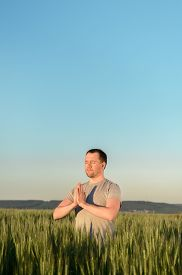Adult Man Stands On A Field In Tall Grass Doing Yoga During Sunset. Digital Detox, Connection With N