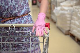 Woman In Protective Glove With A Shopping Trolley In A Supermarket. Pandemic Times Shopping. Selecti