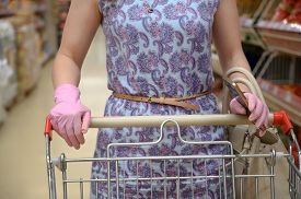 Woman In Protective Glove With A Shopping Cart In A Supermarket. Pandemic Times Shopping. Selective