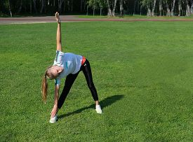 Teenage Girl Doing Exercises Outdoors. Blonde Girl Alone Training At Stadium. Social Distance Concep