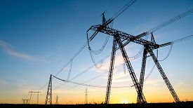 Silhouettes Of High Voltage Pylons At Sunset. High Voltage Power Lines In The Evening Sky. Copy Spac