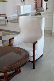 White Modern Chair. White Velvet Armchair Of Old Design On Short Legs With High Back