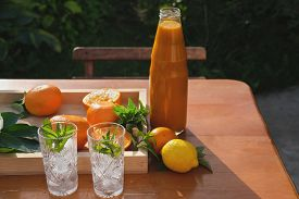Orange Juice And Oranges On The Table. Ice Cubes In Trendy Crystal Glasses With Peppermint Leaves. C