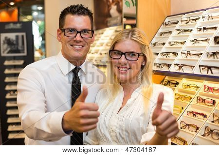 Customers in optician's shop choosing the right frame for eyeglasses from a shelf with many different models and showing thumbs up poster