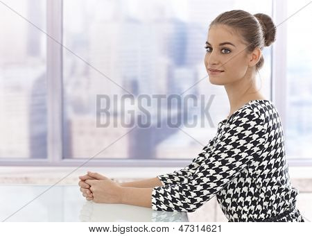 Attractive young businesswoman sitting at table in bright room.