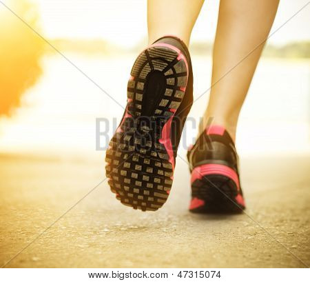 Runner feet running on road closeup on shoes. Woman fitness sunrise jog workout welness concept poster