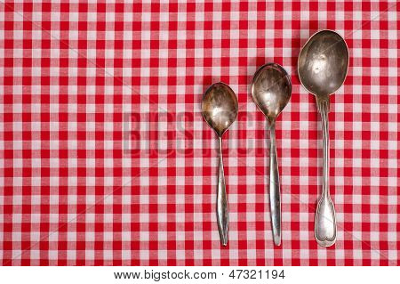 Red And White Checked Table Cloth With Old Spoons