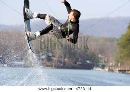 Teenage boy sideways during a flip on the wakeboard poster