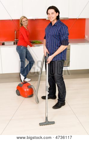 Man Vacuuming, Woman Standing In Background