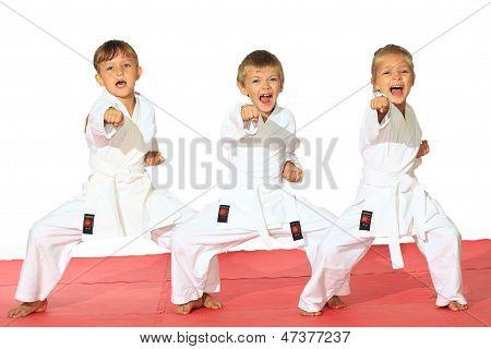 Three children in kimono hit a punch on a white background
