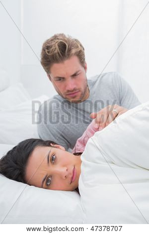 Woman ignoring her partner in her bed during a dispute