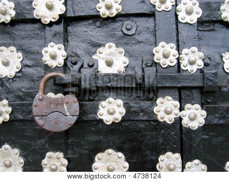 Padlock On Ancient Metalic Door.