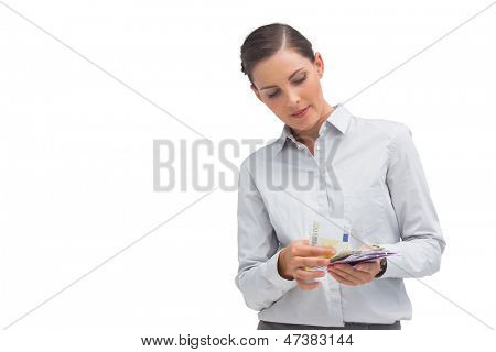Happy businesswoman counting money on white background
