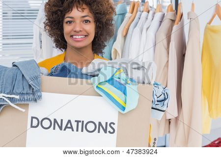 Happy volunteer smiling and holding donation box