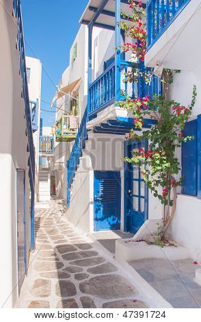 The Narrow Streets Of The Island With Blue Balconies, Stairs And Flowers At Sun.