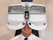 Customer of a optometrist or optician looking through phoropter to determine the right glasses poster