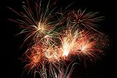 Fireworks streaks and explosions against a black night sky. poster