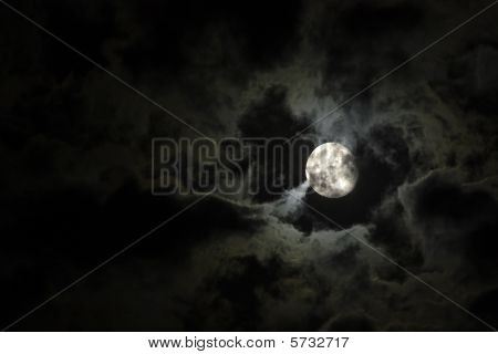 Full Moon And Eerie White Clouds Against A Black Night Sky