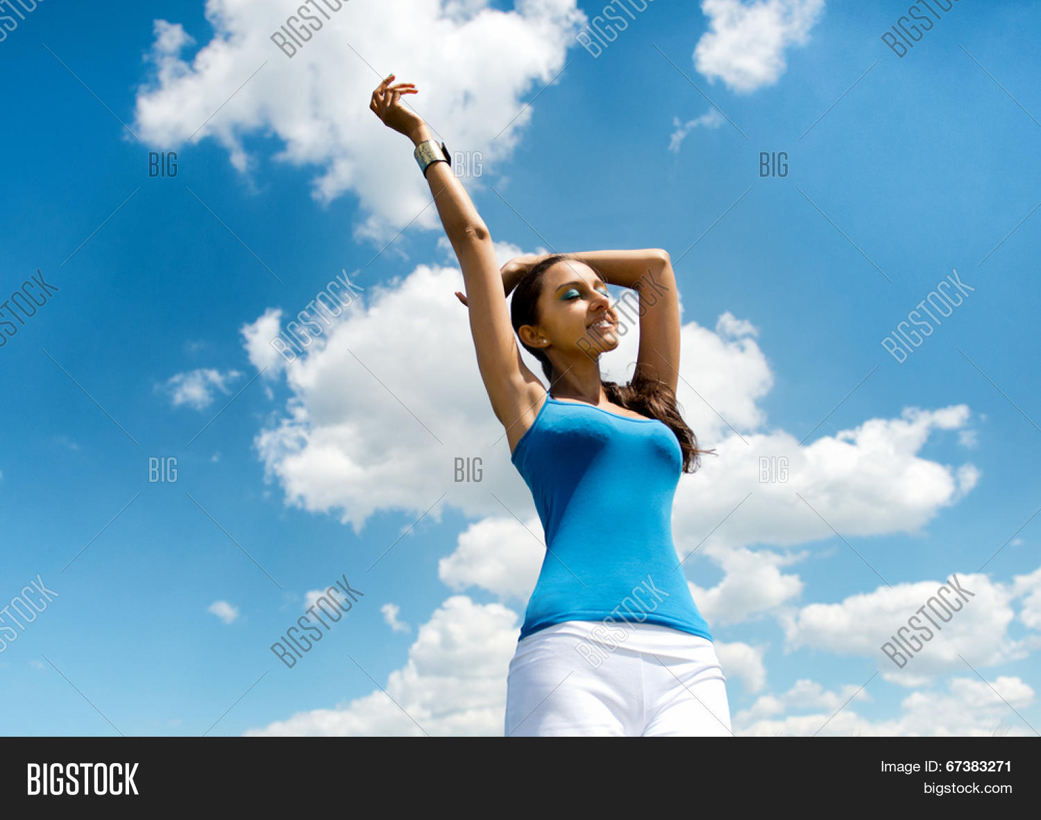 Beautiful busty young woman rejoicing in the sun standing against a sunny  blue summer sky with