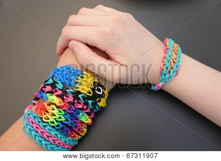 Loom band craft is a global trend. Teenage girls model their loom band friendship bracelets. poster
